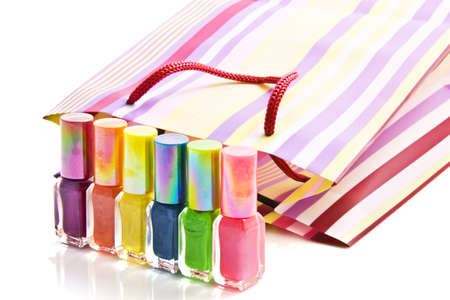 Colorful nailpolish in front of a striped bag isolated over white Stock Photo - 7646789