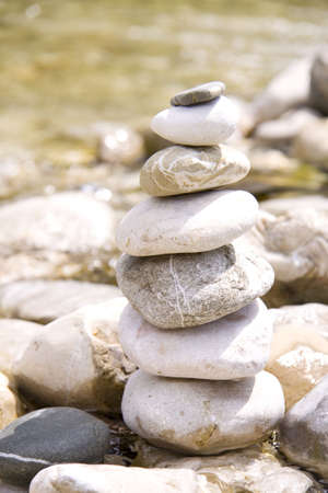 Pile of stones near a river in balance photo