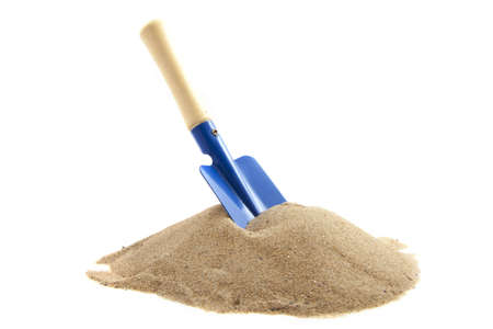 Pile of sand with spade isolated over white