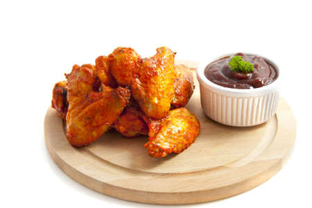 breaded: Chicken wings on wooden plate isolated over white Stock Photo
