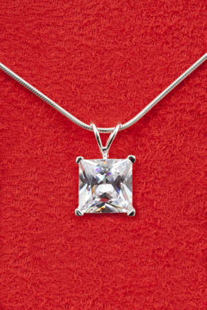 Shiny diamond on a necklace isolated over red Stock Photo - 8506692