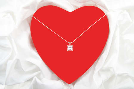 Red heart with diamond on necklace isolated over satin Stock Photo - 8506308