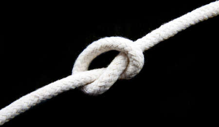 devour: Knot in a white rope isolated over black