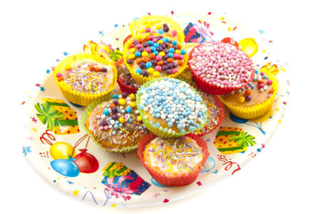felicitation: Colorful sweet cup cakes on a decorated plate isolated over white