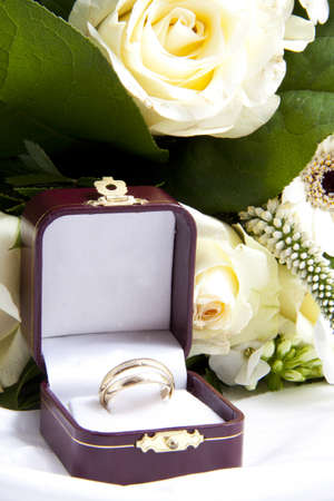 Rings in box on satin with white roses photo