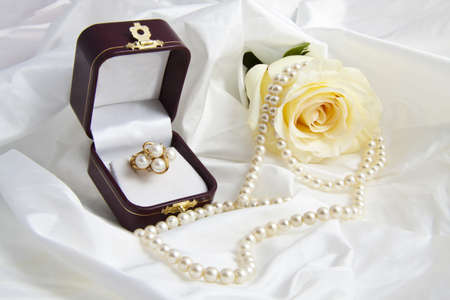 mariage: Golden ring with pearls and rose in a gift box on a satin background