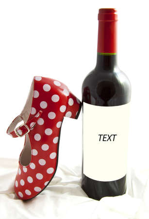 Bottle with red wine and spanish dotted red white shoe isolated on satin Stock Photo - 8808740