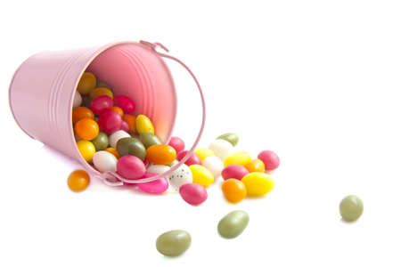 Pink bucket with colorful candy eggs over white photo