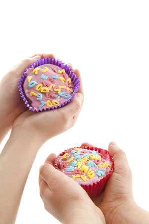 Two decorated cupcakes holding in child hands over white photo