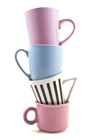Vier farbige Tassen auf einem Stapel in weiß