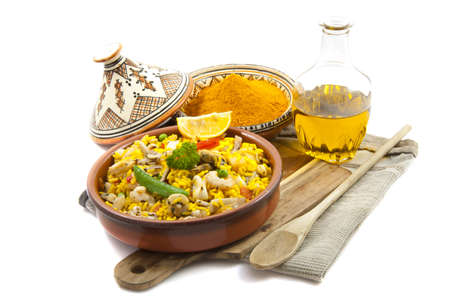 Paella with saffron and oil isolated over white photo
