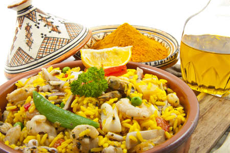Paella with saffron and oil on a wooden board over white photo