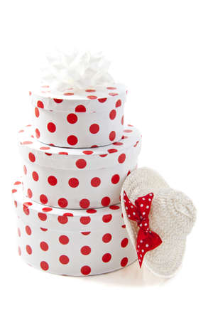 three gift boxes: Three round spotted gift boxes on a pile with straw white hat over white