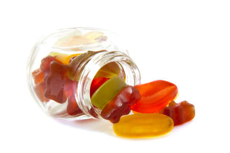 Spilled candy and a jar isolated over white Stock Photo - 10626532