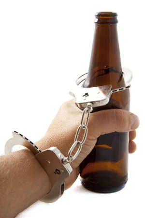 Hand with handcuffs and bottle of beer photo