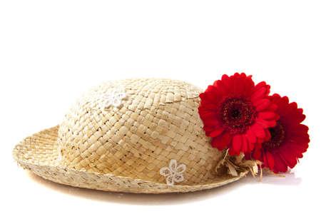 straw hat: Cappello di paglia con due rossi di gerbera su bianco Archivio Fotografico