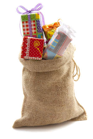 Bag of jute filled with presents isolated over white photo