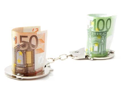 manacles: Dinero en las esposas sobre un fondo blanco Foto de archivo