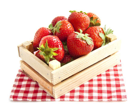 chequered: Fresh strawberries in wooden box on red white chequered napkin over white Stock Photo