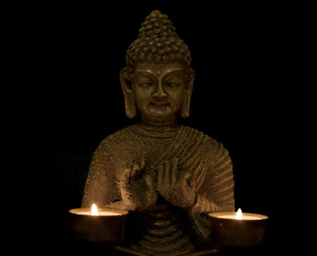 budha with two candles on a black background photo