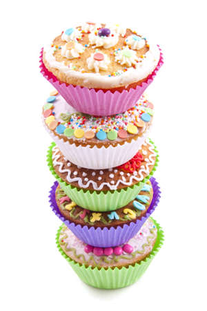 Delicious colorful cupcakes on a pile over white photo