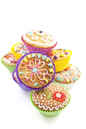 Colorful decorated cupcakes on a pile over white photo