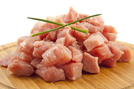 Raw pork on a wooden plate isolated over white photo