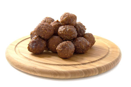 Fresh little meatballs on a wooden plate over white