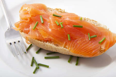 Delicious salmon on bread with a fork on white plate photo
