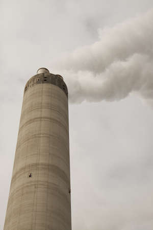 Big large chimney with a lot of smoke in front of a cloudy sky photo
