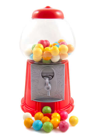 Colorful gumballs in and in front of gumball machine isolated over white photo
