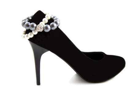 Black high heel shoe with bracelet pearls isolated over white photo