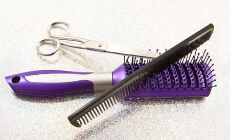 Purple brush comb and scissors on a glittering background photo