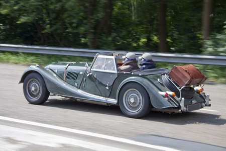 silver sports car: Old classic car driving on the highway for background use Editorial