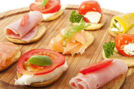 Fresh delicious tapas on a wooden plate for background use photo