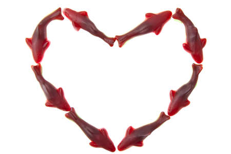 Shape of a  heart with red candy shark isolated over white photo