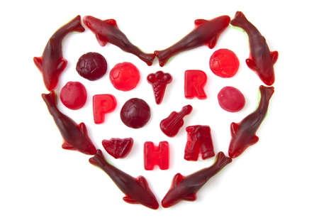 Colorful candy figures in shape of a heart isolated over white photo