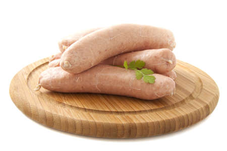 Fresh sausages on a wooden plate isolated over white photo