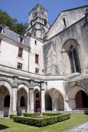 restauration: Old church of brantome with little fountain in the garden