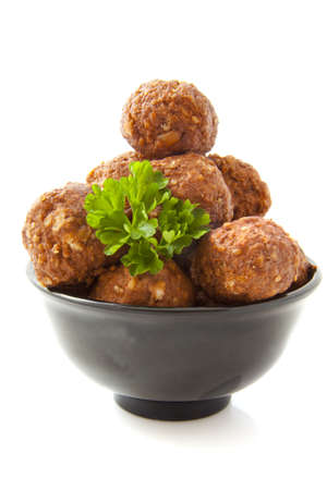 mincing: Meat balls in a black bowl isolated over white Stock Photo