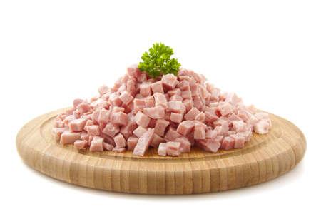 pancetta cubetti: Pezzi di prosciutto su piastra in legno isolato su bianco