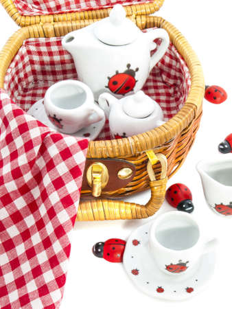 Picnicbasket filled with dishware and ladybugs for background use