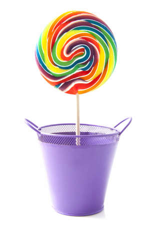 lollypop: Colorful rainbow lollipop in purple flowerpot isolated over white Stock Photo