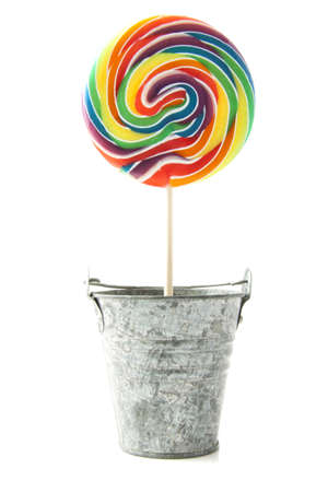 sweet tooth: Colorful rainbow lollipop in zinc bucket isolated over white