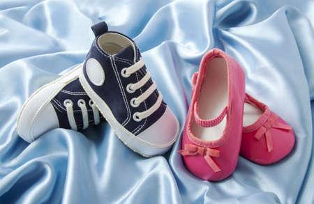 niñas gemelas: Zapatillas de deporte azules de bebé y pequeños zapatos de bebé rosados ??del ballet en el satén azul Foto de archivo