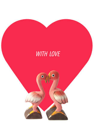 Two handmade flamingos in front of red heart isolated over white photo