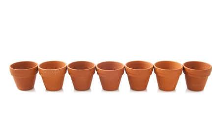 ollas de barro: Macetas de cerámica de color naranja en una fila aislado más de blanco Foto de archivo