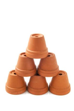 flowerpots: Ceramic orange flowerpots on a pile isolated over white