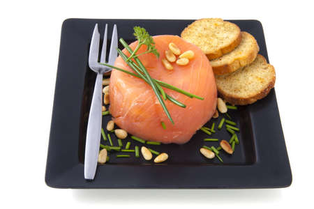 Smoked salmon fillet with parsleyon a black plate  isolated over white photo