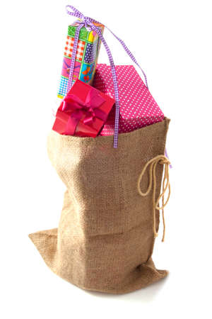 Jute bag filled with gifts isolated over white photo
